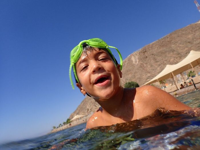 Portrait of smiling boy swimming in sea during sunny day