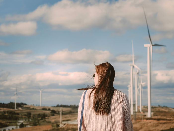 Asian woman with sunglasses see to sky for her boyfriend take photo with wind turbine background