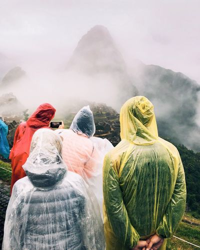 People looking at mountains during foggy weather