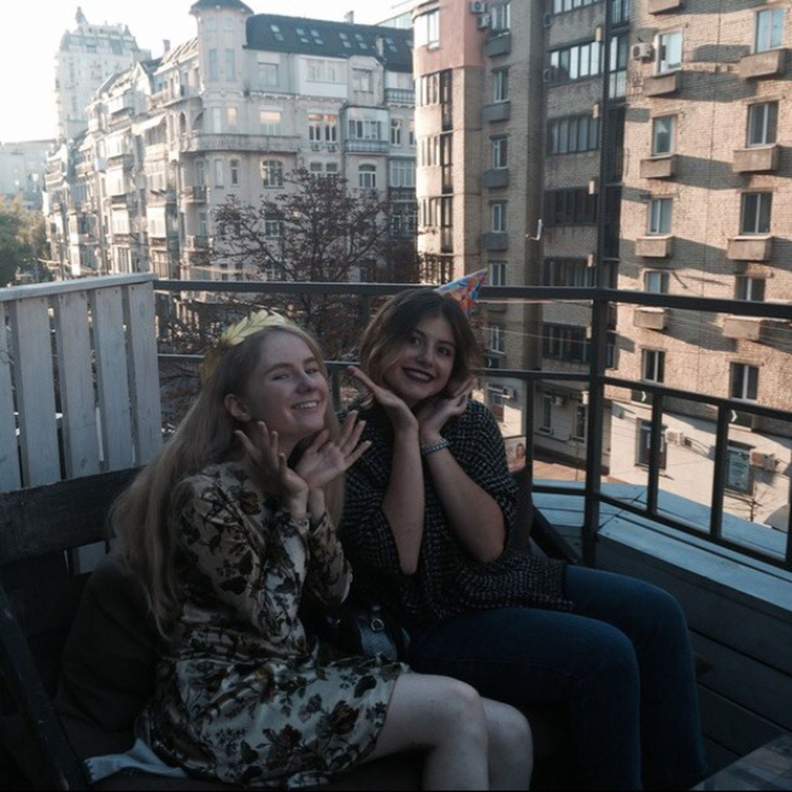 togetherness, building exterior, city, architecture, friendship, young adult, looking at camera, bonding, built structure, young women, portrait, love, casual clothing, lifestyles, city life, smiling, leisure activity, happiness, toothy smile, front view, person, long hair, embracing, enjoyment, beautiful people, outdoors, affectionate