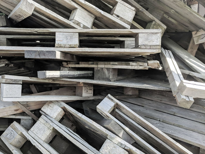 Full frame of wooden cargo pallets in a disorderly pile