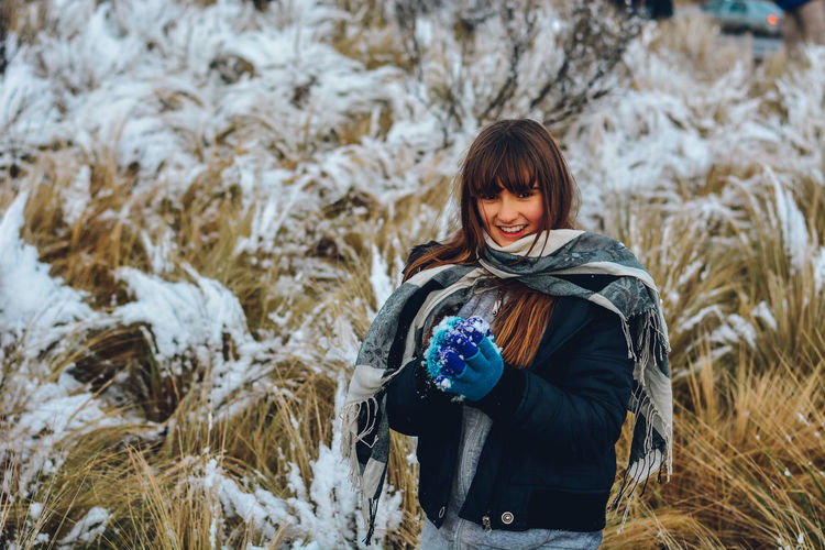 Portrait of smiling woman on snow covered field
