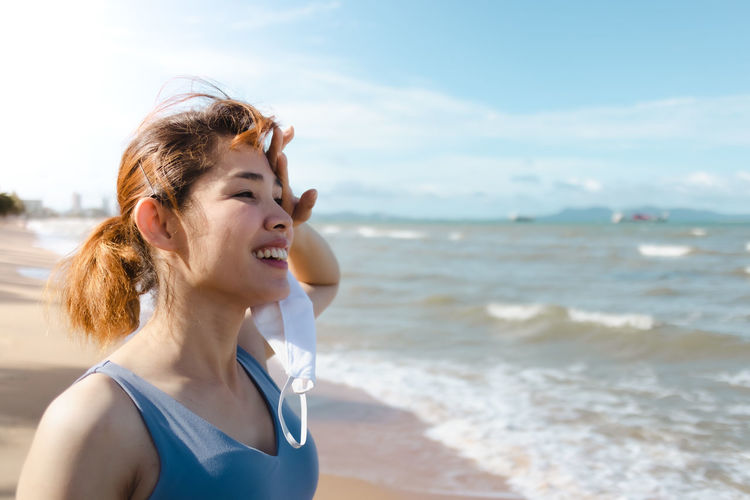 Young woman on beach against sky