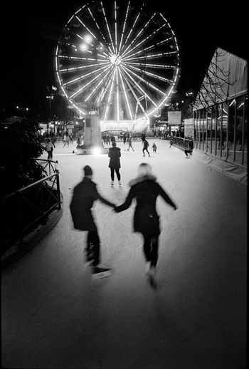 Skating in Oslo centre. Analogue Night Illuminated Leisure Activity Real People City Group Of People Lifestyles Motion People Ferris Wheel Street Incidental People Outdoors Analogue Photography Streetphotography Streetphoto_bw 35mm Film 35mmfilmphotography Oslo Couple Playful Holiday Moments Human Connection