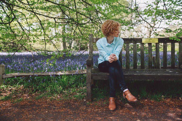 Full length of woman sitting on wooden bench against plants at forest
