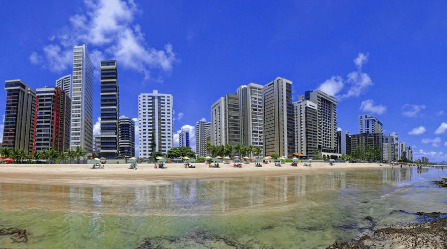 Panoramic view of modern buildings against blue sky