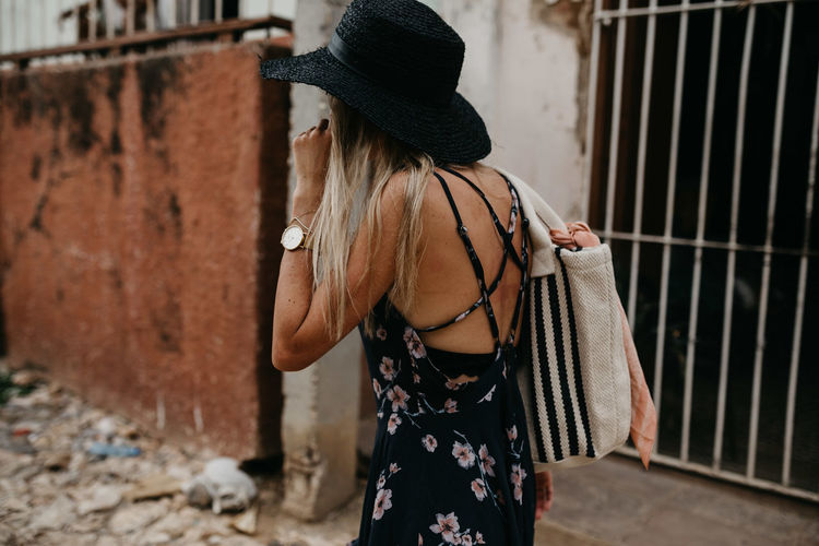 Side View Of Young Woman Wearing Hat While Standing On City Street