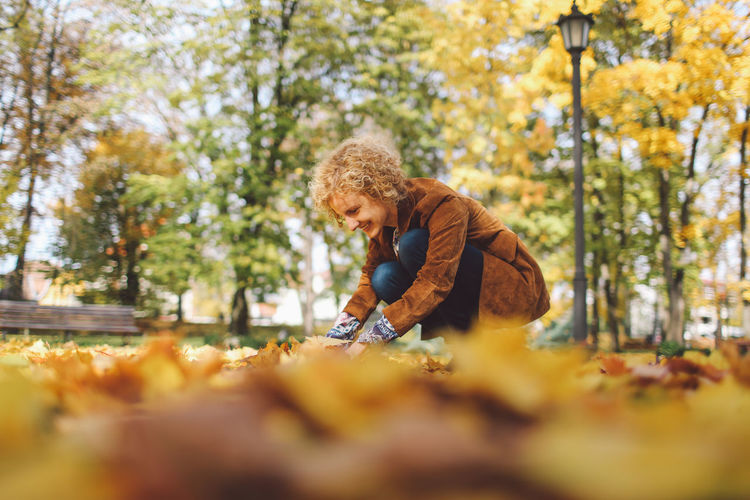Young woman playing with autumn leaves at park