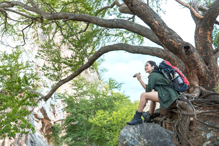 Young man sitting on tree trunk