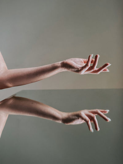 Midsection of woman with arms raised against gray background