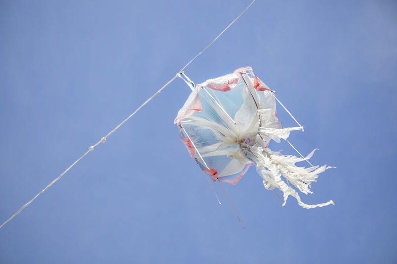 Low angle view of decoration hanging from rope against sky
