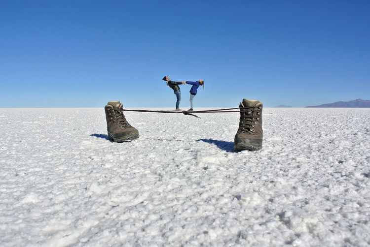 Man and white umbrella on land against clear blue sky
