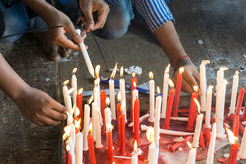 People igniting candle in church