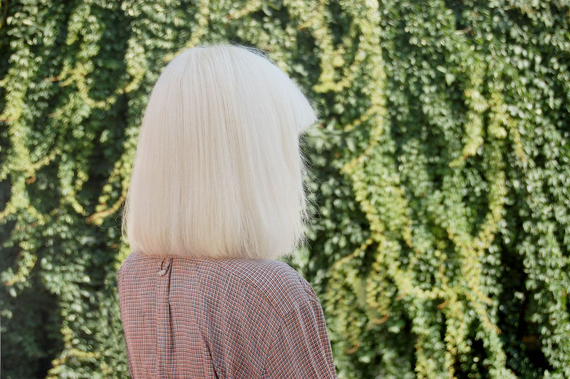 Woman looking away standing against plants