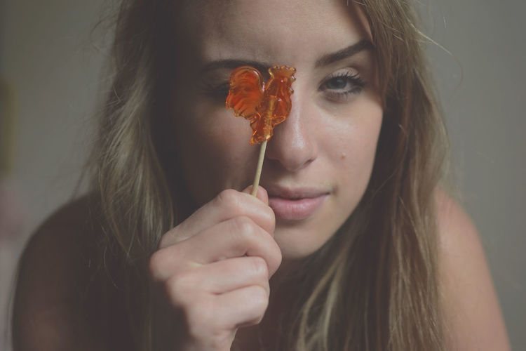 Close-Up Of Beautiful Young Woman Holding Lollipop