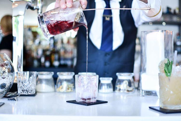 Midsection of bartender preparing drink