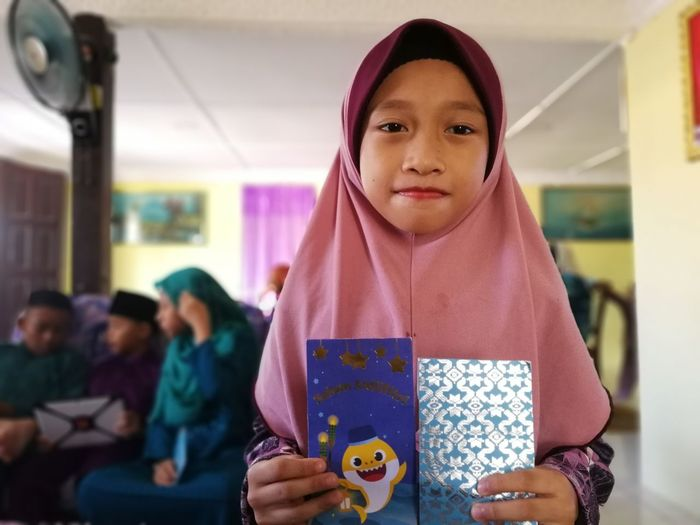 Portrait of girl holding greeting cards at home