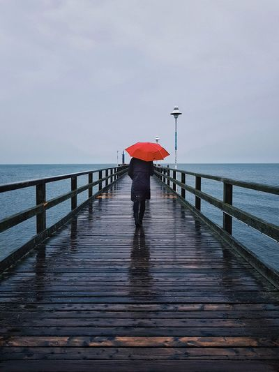 Rear view of woman standing on pier at sea during rainy season