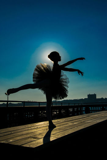 Silhouette ballerina dancing on wooden table at pier against sky during sunny day