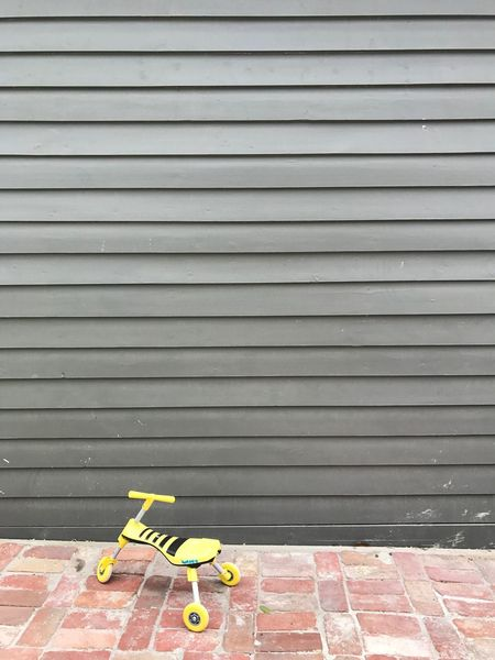 Architecture Asphalt Bricks Day Gray Grey Grey Wall No People Outdoors Pattern Rule Of Thirds Solitary Suburban Suburban Landscape Tricycle Trike Trikebike Wall Yellow Toy Yellow Tricycle