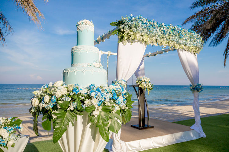 wedding cake in the outdoor wedding ceremony setting nearby the sea Wedding Wedding Photography Beach Beauty In Nature Blue Bouquet Cake Close-up Day Flower Horizon Over Water Nature No People Outdoors Scenics Sea Sky Sunlight Tranquil Scene Tranquility Tree Vase Water Wedding Cake White Color