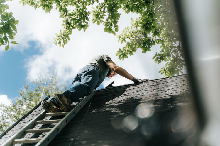 Low angle view of man against climbing on roof