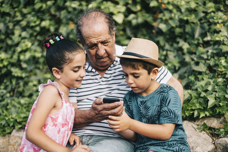Cute boy wearing hat using smart phone while sitting with grandfather outdoors