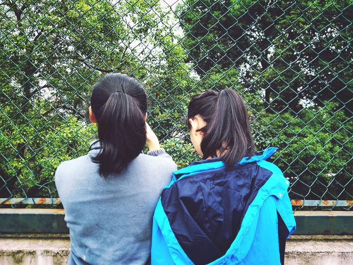 Rear View Of Female Friends Against Chainlink Fence