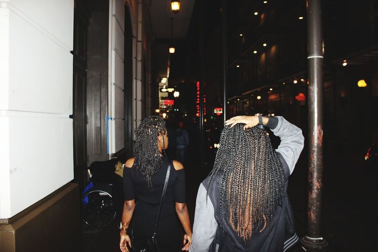 Women Walking On Sidewalk Of City Street At Night