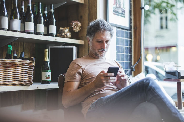 Mature owner using smart phone while sitting on chair in deli
