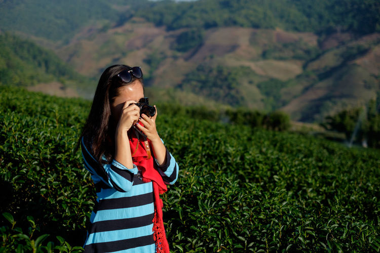 Side view of girl taking photo at tea plantation. ThatsMe Beauty In Nature Camera Camera - Photographic Equipment Day Digital Camera Digital Single-lens Reflex Camera Field Growth Holding Landscape Leisure Activity Lifestyles Mountain Nature One Person Outdoors Photographer Photographing Photography Themes Real People Scenics SLR Camera Standing Technology Women