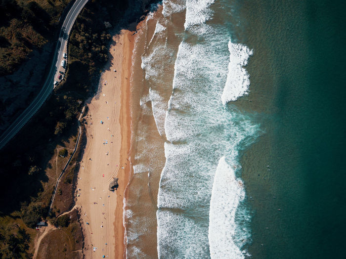 High angle view of beach with waves and surfers