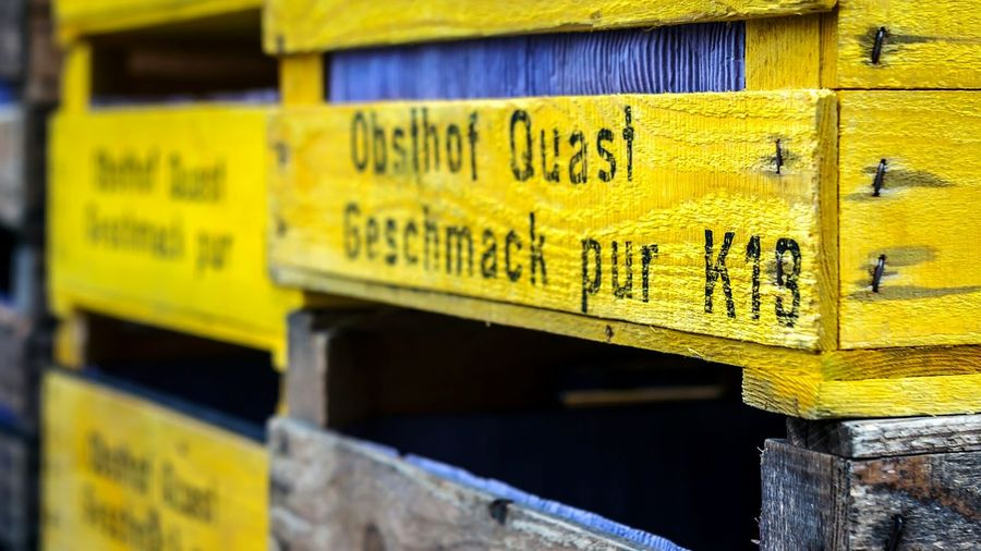 Close-Up Of Text On Yellow Painted Wooden Boxes