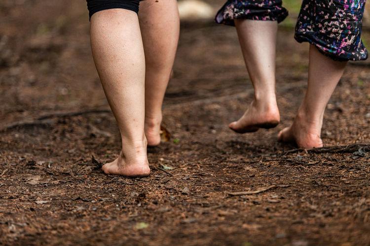 Low section of women walking in mud