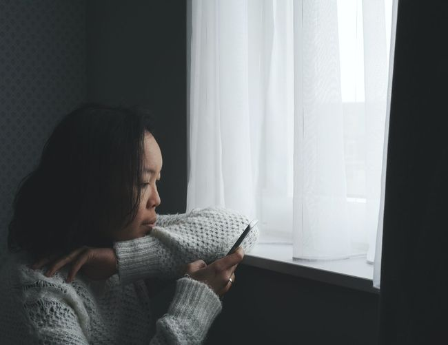 Close-up of woman using phone at window