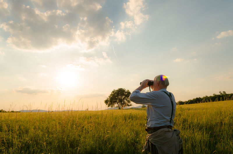 Rear View Of Man Using Binoculars On Field Against Sky During Sunset
