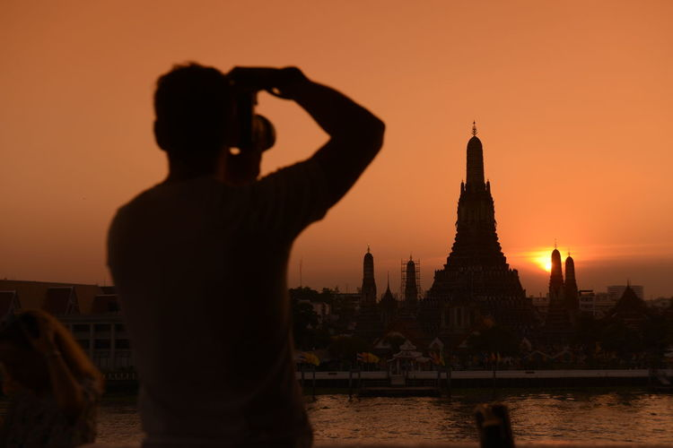 Rear view of man photographing wat arun temple against sky during sunset