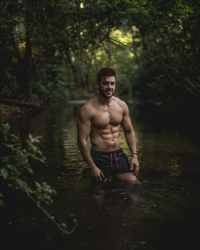 Full length of shirtless man in forest