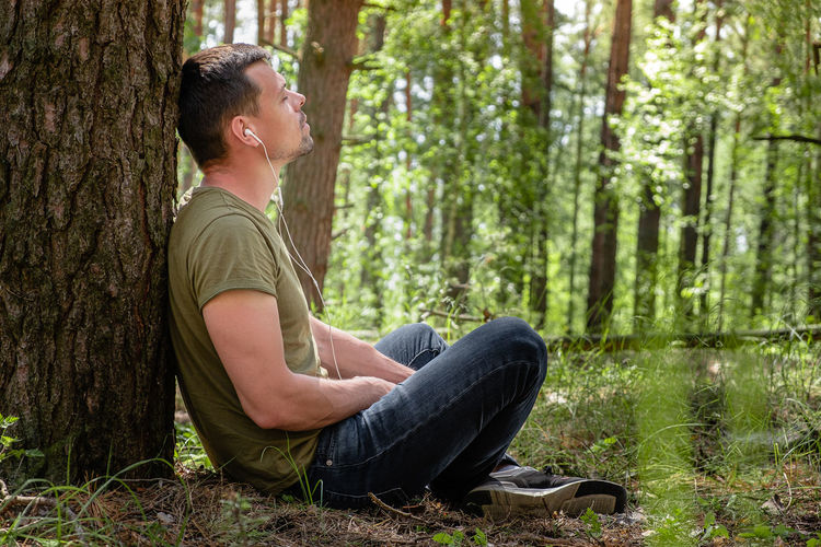 Side view of young man sitting on tree trunk in forest
