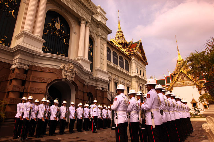 Military officers standing outside temple against sky