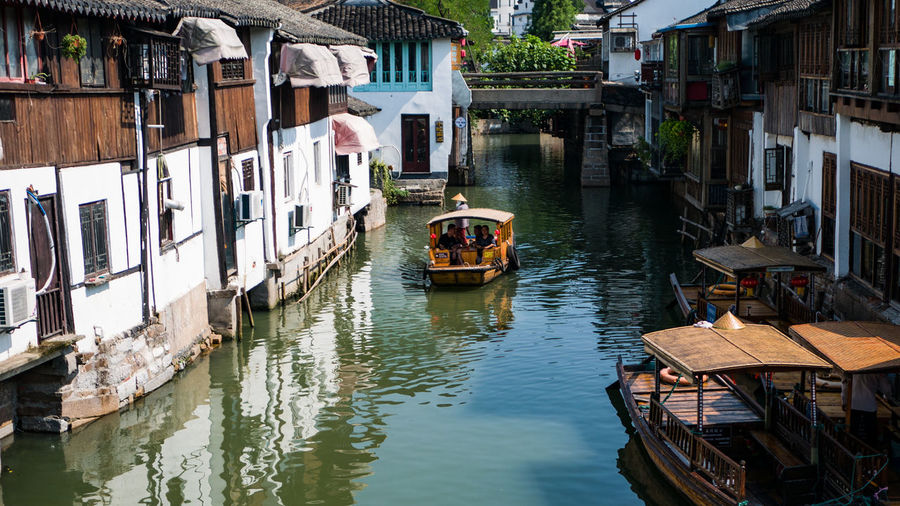 Boat going down a canal. Water Nautical Vessel Waterfront Residential Building Canal House Architecture Building Exterior Built Structure Rowboat Old Town Boat Rowing Town Water Vehicle