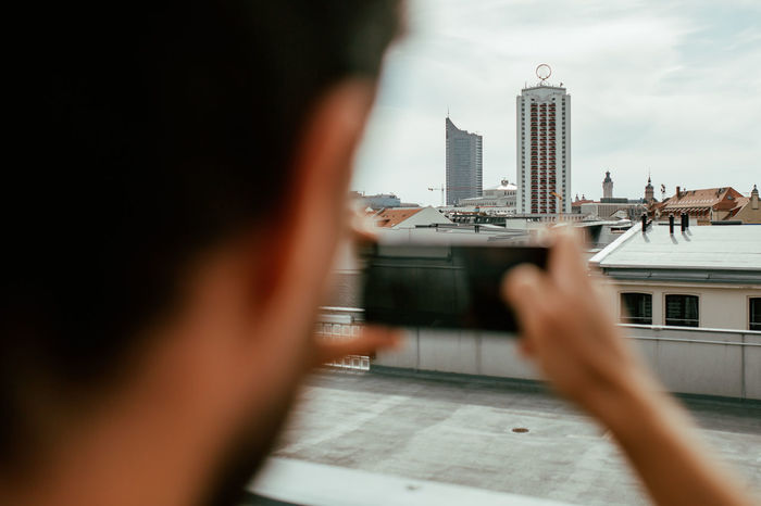 Man photographing cityscape through mobile phone
