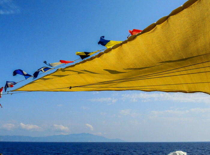 Sailing to the Giglio Island (Tuscany-Italy) Blue Blue Color Blue Sea Clouds And Sky Day Flag Pole Flags Flags In The Wind  Fluttering Horizon Over Water No People Outdoors Sail Sailboat Sailing Sea Sea And Sky Ship At Sea Sky Sky And Clouds Water Wind Yellow Color Yellow Sail