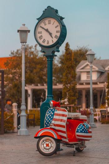 Clock on street against buildings in city