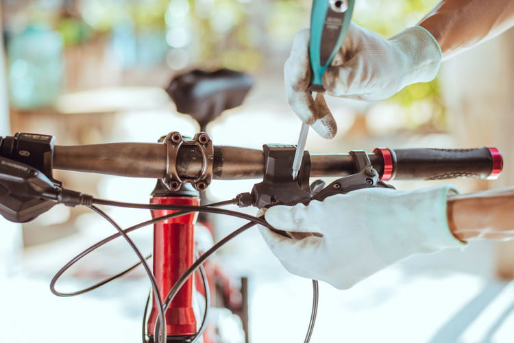 Cropped hands of person repairing bicycle