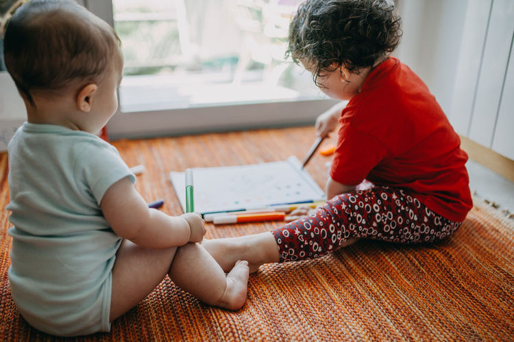 Cute childs sitting on drawing at home