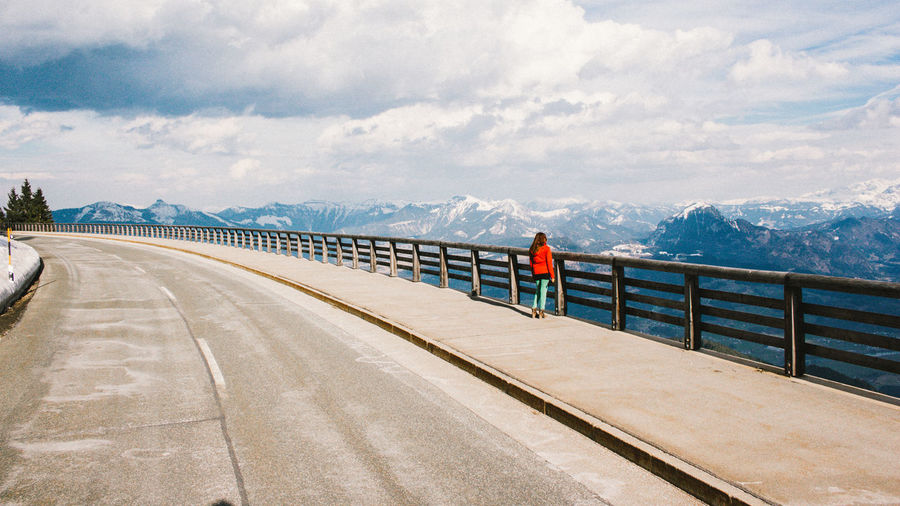 Rear view of woman standing on bridge by mountains