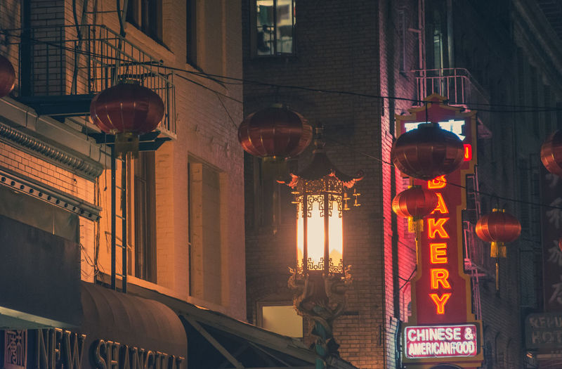 Low angle view of illuminated lanterns hanging on street by buildings