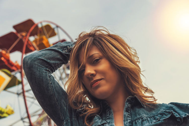 Lovely young woman in a Luna Park shortly before sunset in autumn Headshot One Person Focus On Foreground Portrait Young Adult Young Women Real People Lifestyles Leisure Activity Hair Women Hairstyle Beautiful Woman Long Hair Front View Beauty Casual Clothing Adult Blond Hair Contemplation Woman Ferris Wheel Ferris Wheel Sunset Looking At Camera Gorgeous Woman