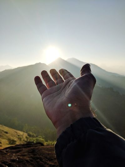 Cropped hand of man gesturing towards mountain against sky during sunrise